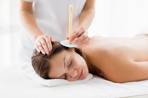 Masseur giving ear candle treatmet to naked woman at spa